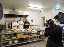 Photographer taking a group photo of pastry chefs in kitchen